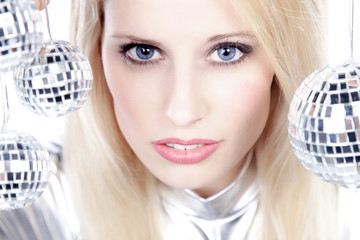 Hübsche blonde Frau mit Discokugeln cool blickend, quer