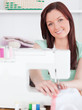 Attractive red-haired woman using a sewing machine in the living