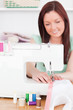 Gorgeous red-haired woman using a sewing machine in the living r
