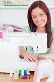 Charming red-haired woman using a sewing machine in the living r
