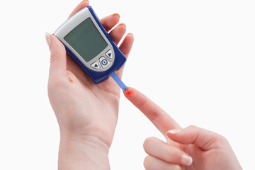 Young woman using a blood glucose meter