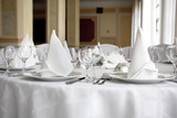 Place settings on an elegant, white dining table in a restaurant poster