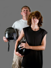 Bikers together - father and teen son holding motorcycle helmets
