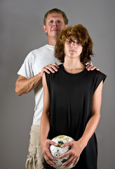 Proud father with soccer-playing teenage son