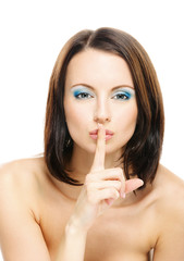 Woman puts forefinger to lips as a sign of silence