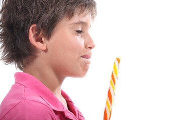 Young boy licking his lips at the sight of his lollypop
