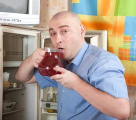 man putting jug into refrigerator