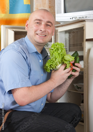 man putting fresh vegetables into fridge