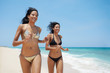 latina sisters in bikini on beach near caribbean sea