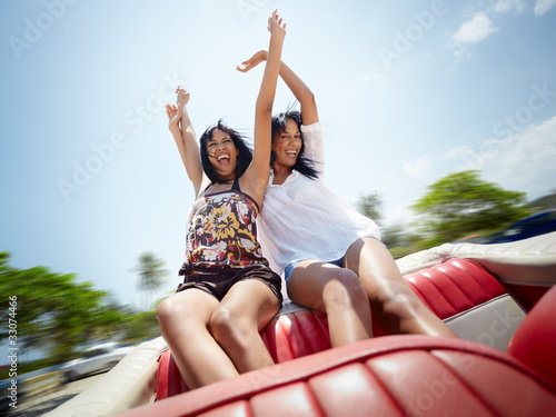 beautiful twin sisters having fun in cabriolet car