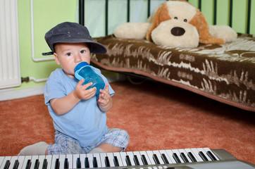 kleiner Junge beim trinken vor Keyboard
