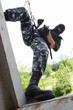 Soldier in mask on rope targeting through the window