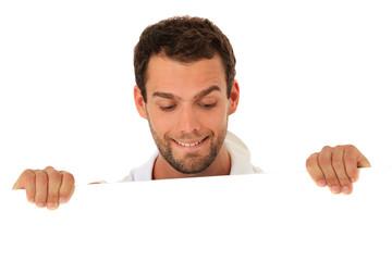 Mann schaut neugierig hinter weißer Wand hervor