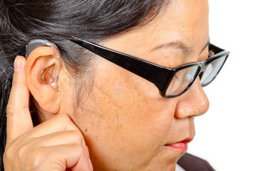 woman with eyeglasses wearing hearing aid