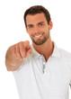 Attraktiver Mann zeigt lächelnd mit dem Finger