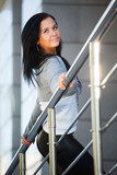 Young woman leaning on the handrail poster