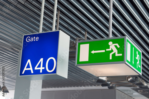 Green emergency exit sign,and blue gate sign in airport