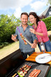 Happy couple cooking meat on barbecue grill