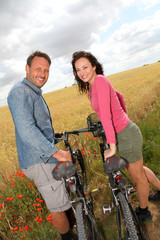 Smiling couple riding bicycle in country field