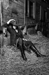 Cowgirl sitting on hay in the stable