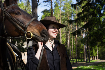 Cowgirl in hat hugging her horse