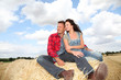 Happy couple sitting on bale in farmland