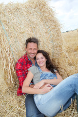 Couple relaxing in hay bales