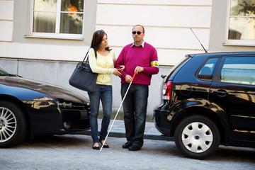Frau hilft blinden Mann über die Straße