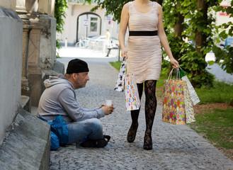 Bettler und reiche Frau mit Einkaufstaschen