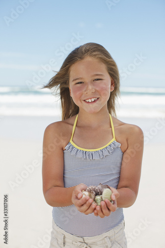 Girl holding shells on beach