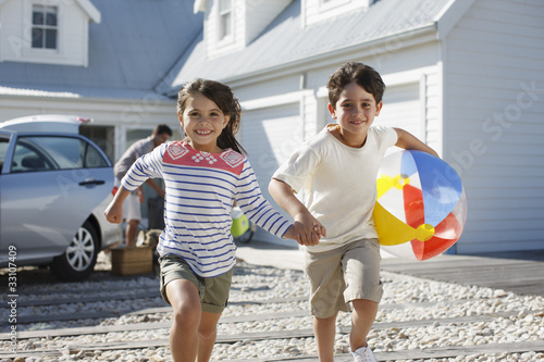 Brother and sister with beach ball running on driveway