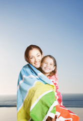 Mother and daughter wrapped in towel poolside