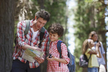 Father and son looking at map in woods