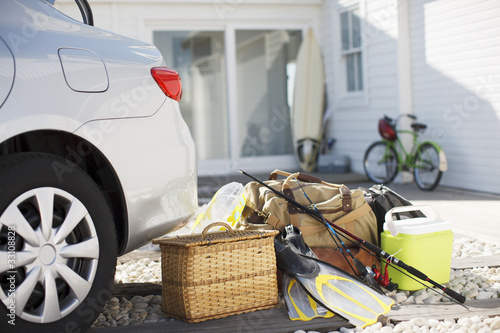 """Picnic basket, fishing rod, flippers and bags outside car in driveway"""