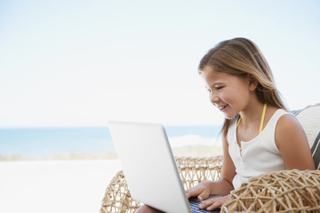 Girl using laptop on beach
