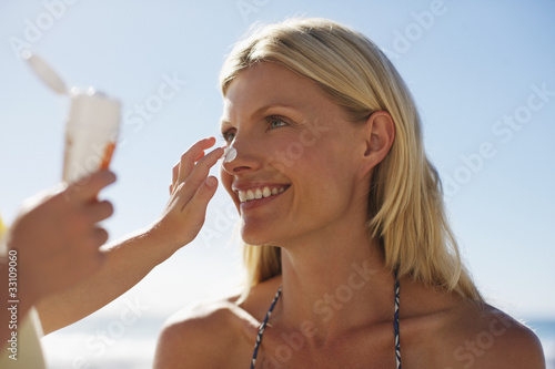 Girl applying sunscreen to mother?s nose