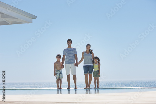Family standing at edge of infinity pool with ocean in background