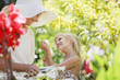 Grandmother and granddaughter picking flowers in garden