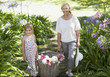 Grandmother and granddaughter with basket of flowers in garden