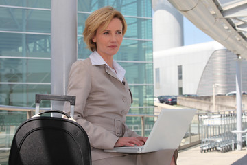 Businesswoman on laptop outside airport