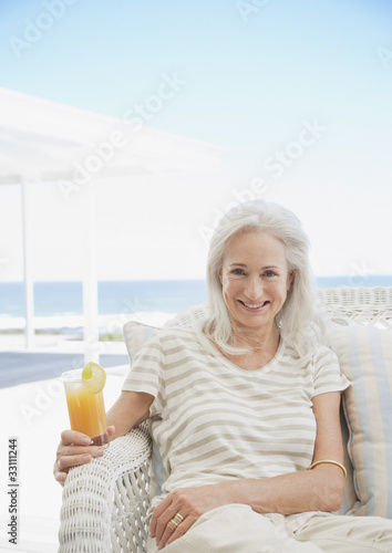 Senior woman drinking cocktail on patio