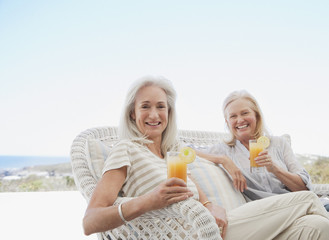 Senior women drinking cocktails on beach patio