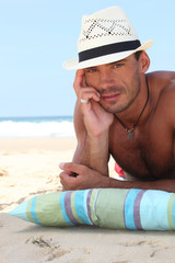 Man on the beach in a straw panama hat
