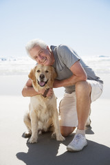 Senior man hugging dog on beach