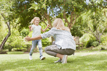 Granddaughter running toward grandmother in yard