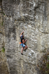 Rock climber on cliff battling his way up
