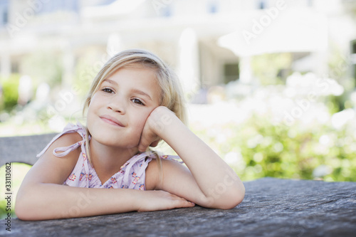 Pensive girl sitting at table outdoors
