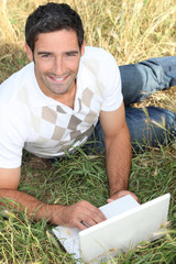 Man lying in the grass using a small laptop computer