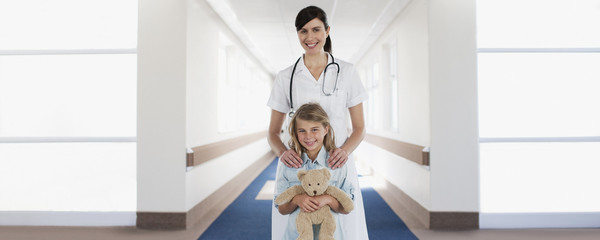 Nurse and child patient with teddy bear in hospital corridor
