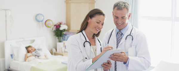 Pediatricians reviewing patient?s medical record in hospital